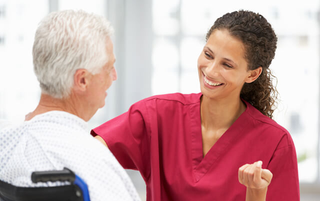 Female nurse with senior male patient in wheelchair smiling
